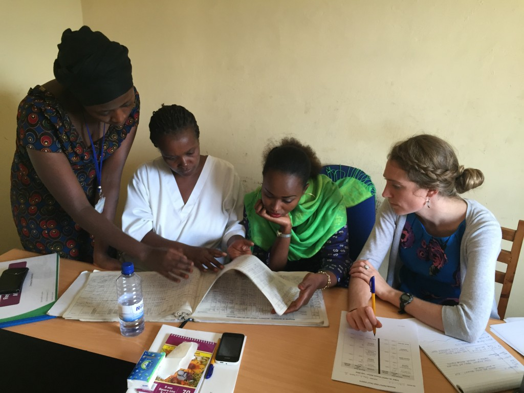 Leigh Tally (right) reviews information with staff members at Murara Health Center, in Rwanda. (Photo by Sara Forhan)