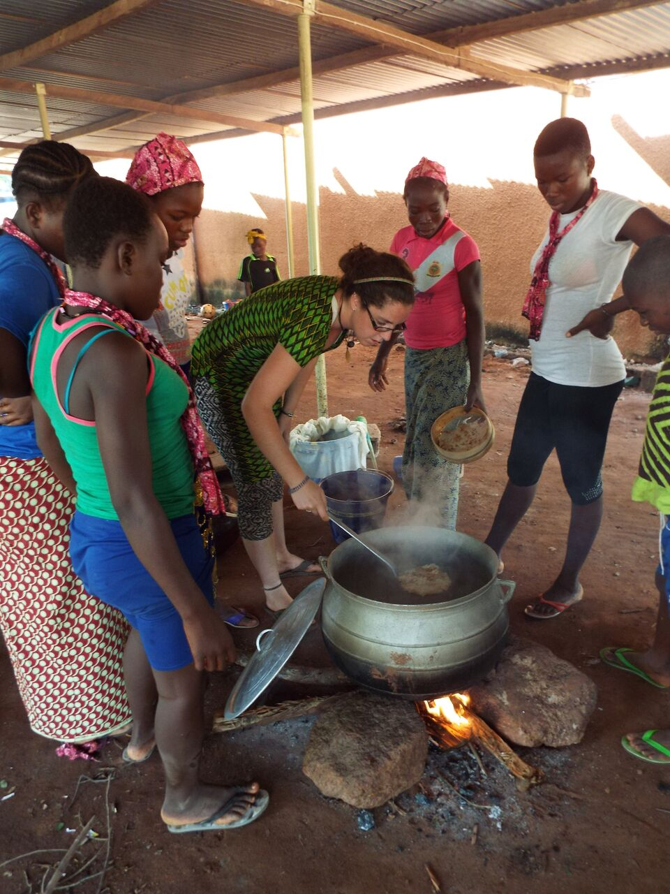 Peace Corps volunteer Charlotte Lane (center) cooks with villagers in Burkina Faso.