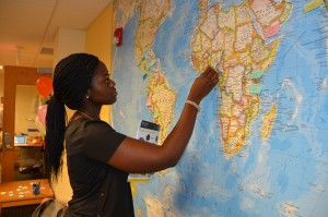 A student marks a world map with the places she has traveled.