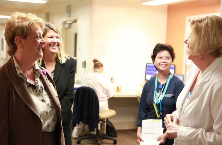 Health care providers and administrators talk in a medical office.