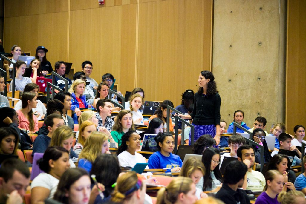 Dr. Kelly Hogan (standing) teaches students in a large, packed auditorium.