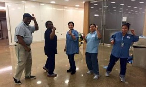 Five members of UNC Chapel Hill's grounds and housekeeping staff are showing off their arm strength after participating in a Fitness Breaks exercise. They are standing in a line, smiling, arms in the air.