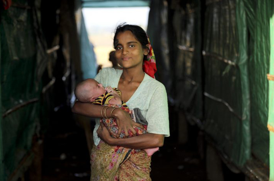 A woman holds a baby in Myanmar.