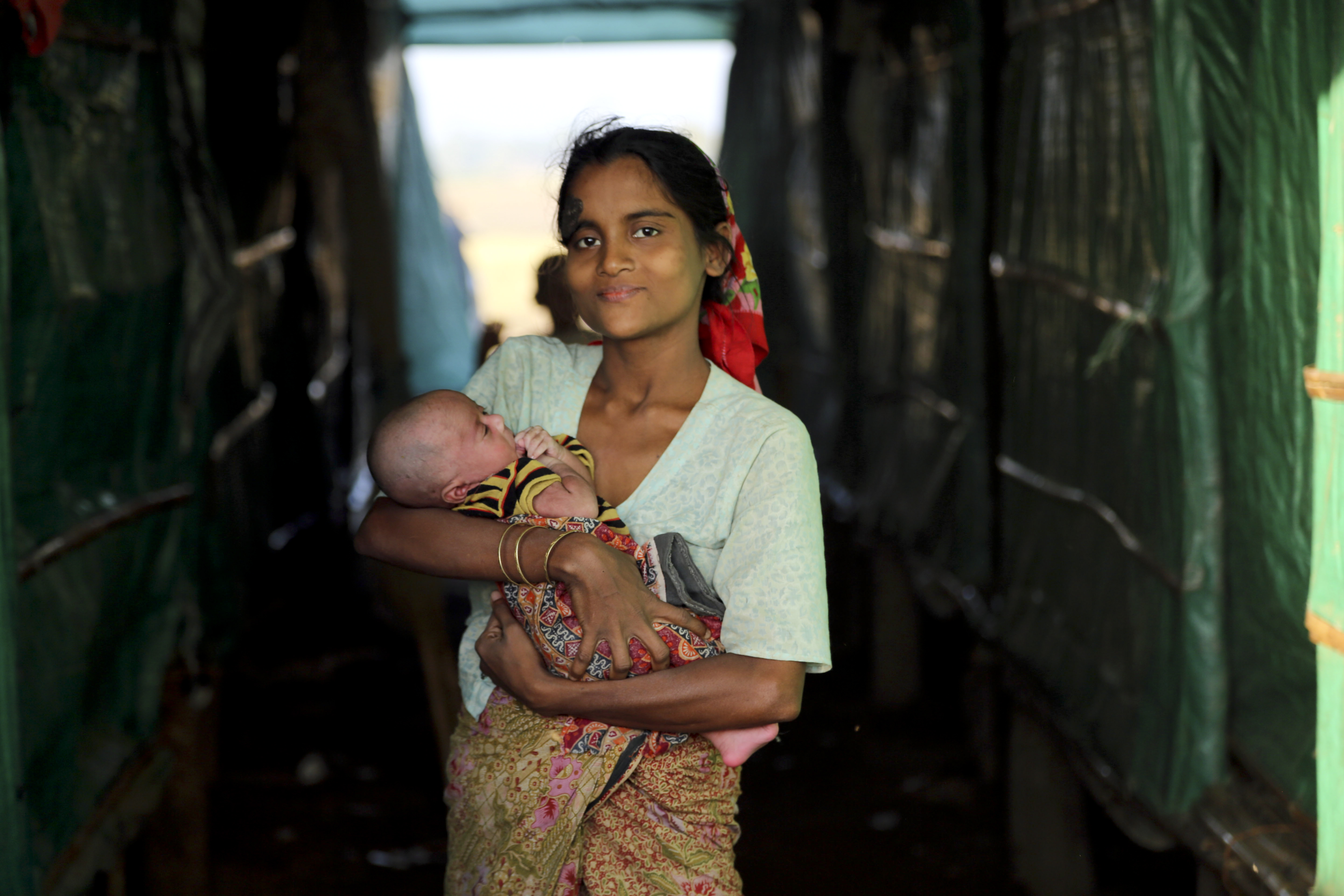 UN Humanitarian Chief Visits Myanmar; a young woman holds her newborn infant.