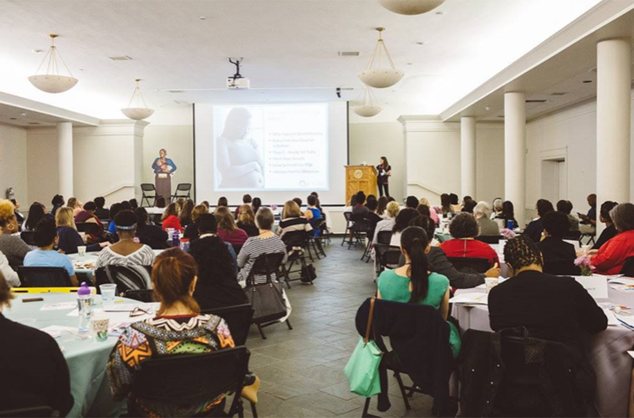 Participants listen to a presentation about pregnant mothers.
