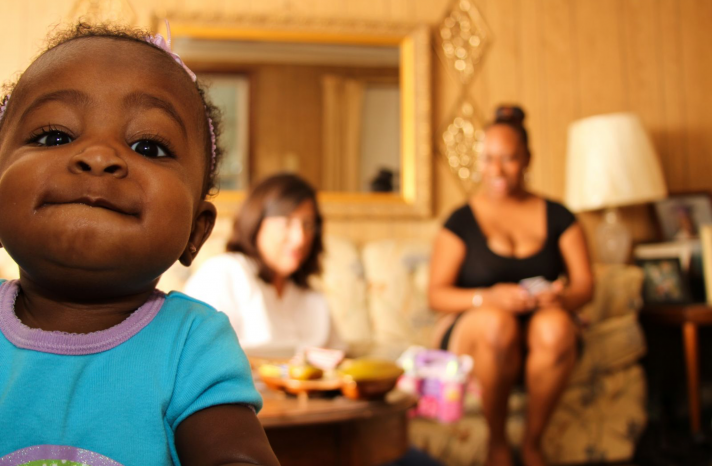 A young toddler smiles for the camera with her mother and a lactation consultant in the background.