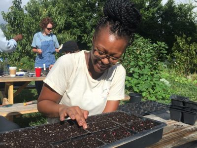 Daijah plants Brussels sprout seeds at Camden Street Learning Garden, a community garden in Raleigh, while volunteering with the Inter-faith Food Shuttle.