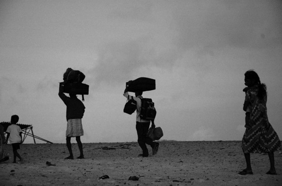People carry boxes above their head in the desert.