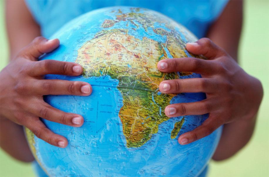 A woman holds a globe.