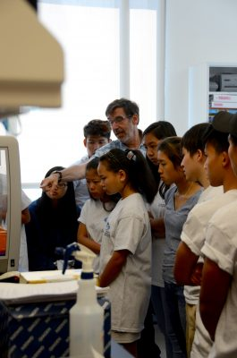 Dr. Steve Meshnick gives refugee high school students a tour of his malaria research lab.