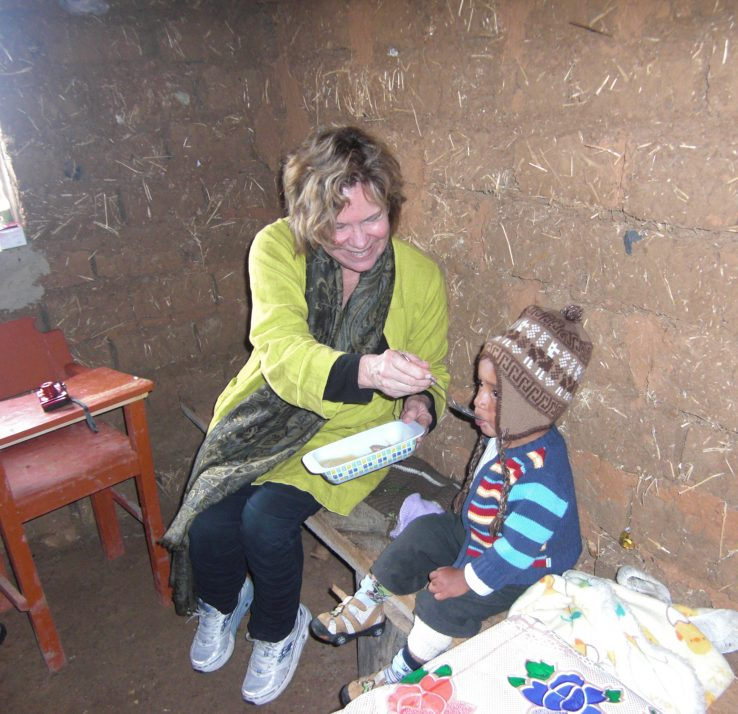 Dr. Peggy Bentley feeds a small child in Peru.