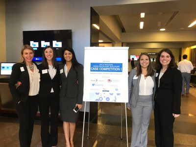 Aditi Borde (in the skirt suit) and Chelsea Anderson (in the light grey suit) represent the Gillings School on their interdisciplinary team. (Contributed photo)