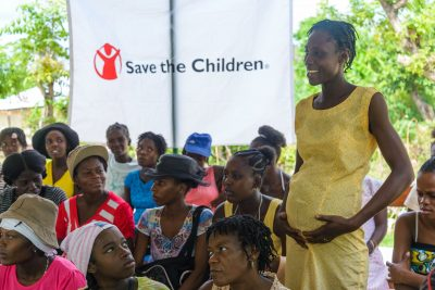 A pregnant woman holds her belly in front of a Save the Children banner.