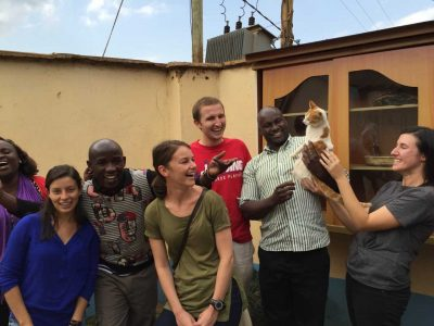 A group poses for a photo; one person holds a cat.