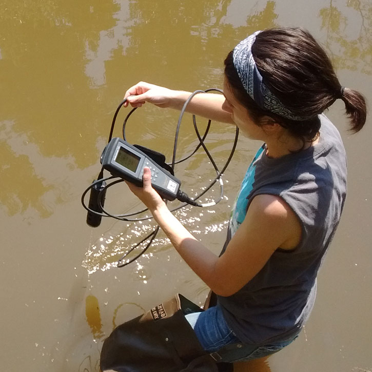 A student takes a water sample.