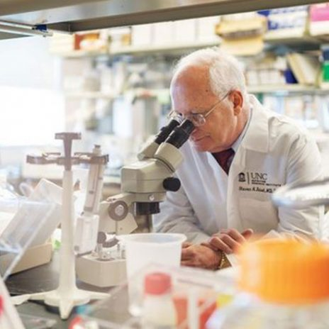 Dr. Steven Zeisel looks into a microscope.