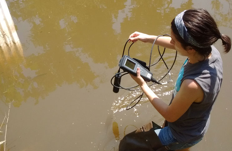Elizabeth Christenson, environmental sciences and engineering student, tests the water quality in a local waterway. As a Boren Fellowship awardee in 2018-2019, Christenson will use her scientific training to work on community-based public health and disease prevention initiatives in the Middle East.