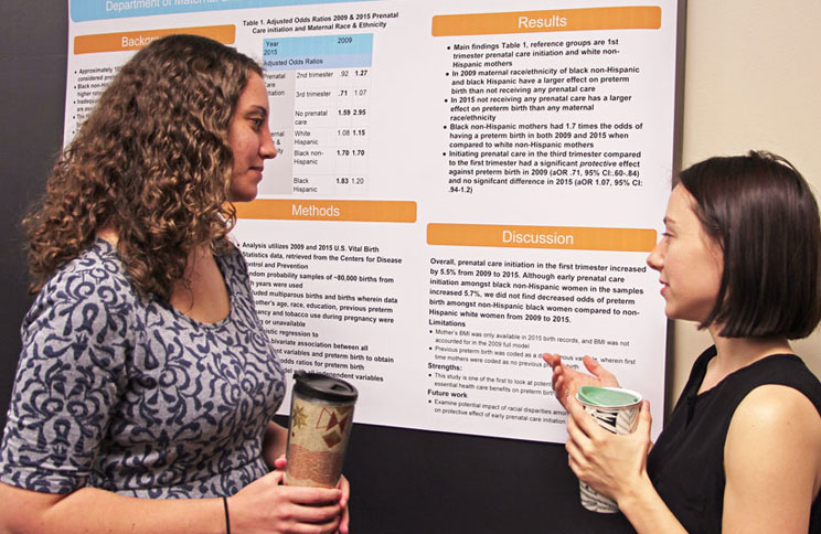 Students chat during a poster presentation.