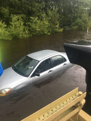 Nate's team passes a submerged car on the highway.