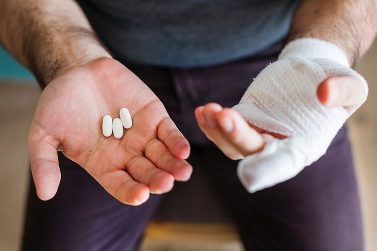 Bandaged hand and pain pills