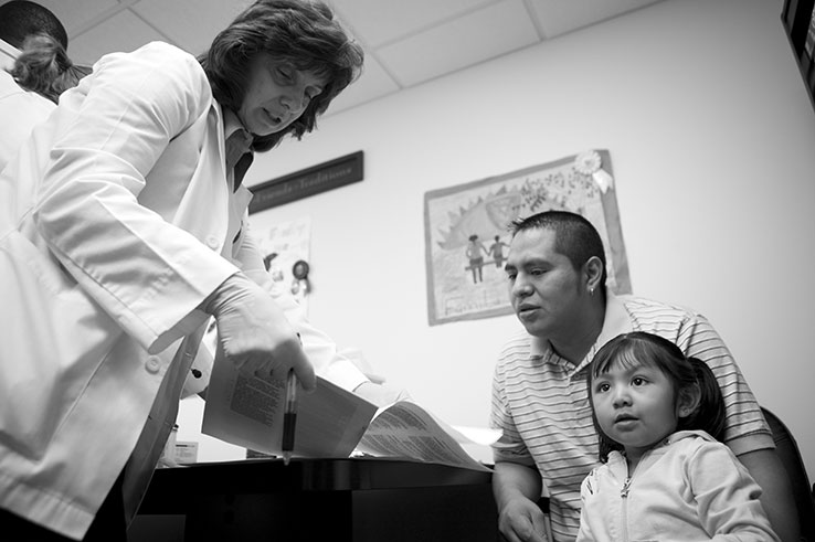 Hispanic father with doctor at medical office. Photo by UMDNJ School of Nursing
