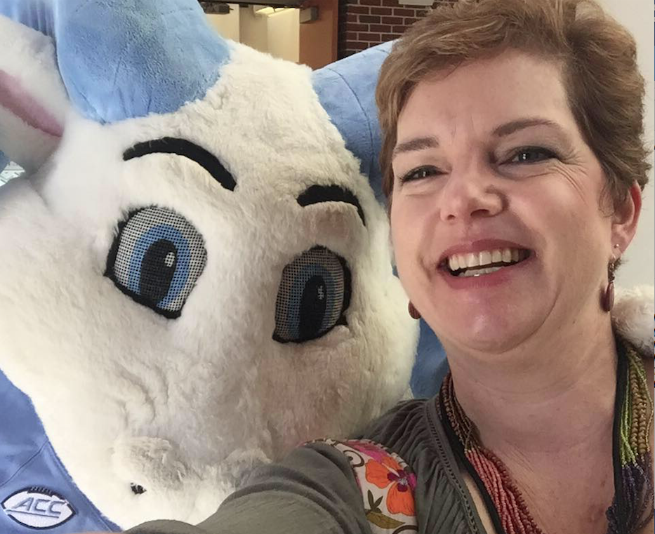 Karen Todd, MD, is all smiles as she poses for a quick photo with Rameses at a campus event.