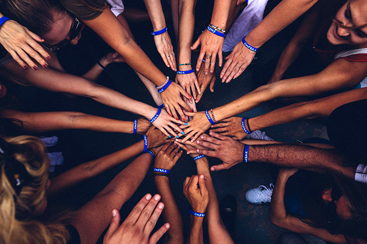 diverse hands in huddle. photo by perry grone/unsplash
