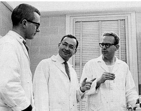 Dr. Charles Weiss (center) consults with two graduate students in a lab at UNC's public health school in the 1960s.