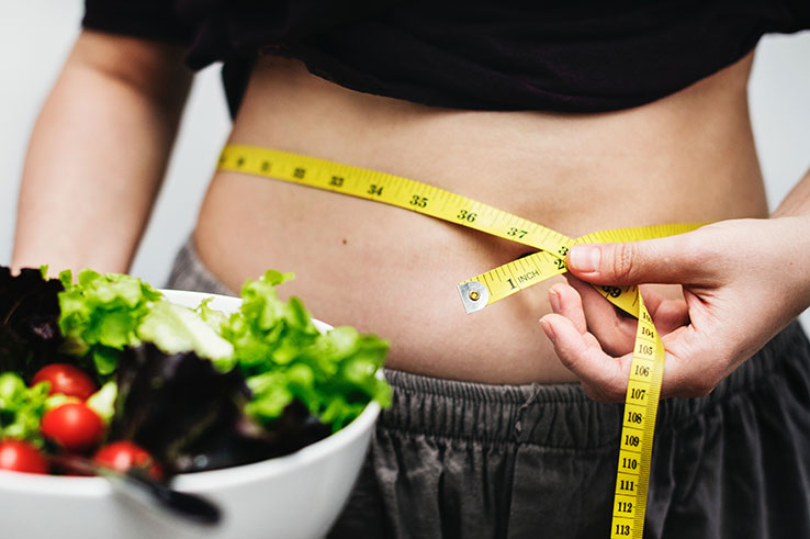 Person measuring waist and holding healthy salad