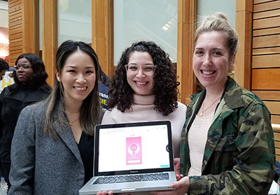 Nicole Gonzalez (center) and Alicia Reynolds (right), members of the winning team, pose with Susanna Choi, Gillings School master's student and event judge (left) and the team's final mobile app product. Not pictured is team member Chelsie Kolberg.