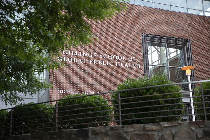 The entrance to the UNC Gillings School of Global Public Health is surrounded by greenery.