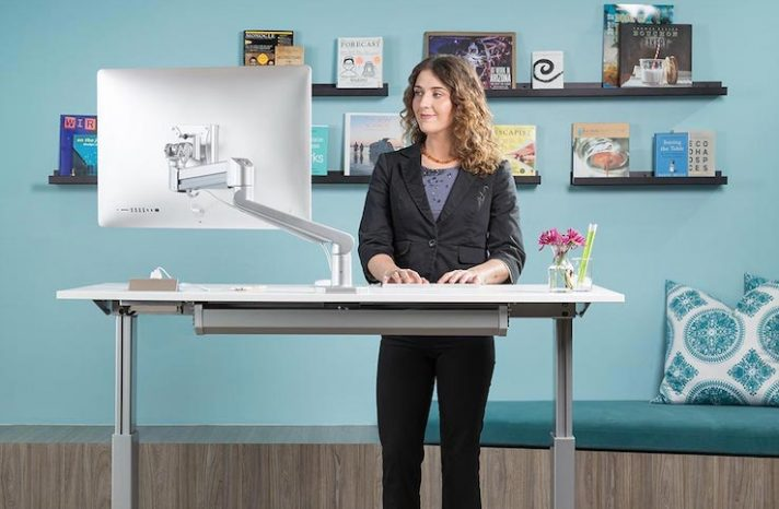 A woman uses a standing desk in her office.
