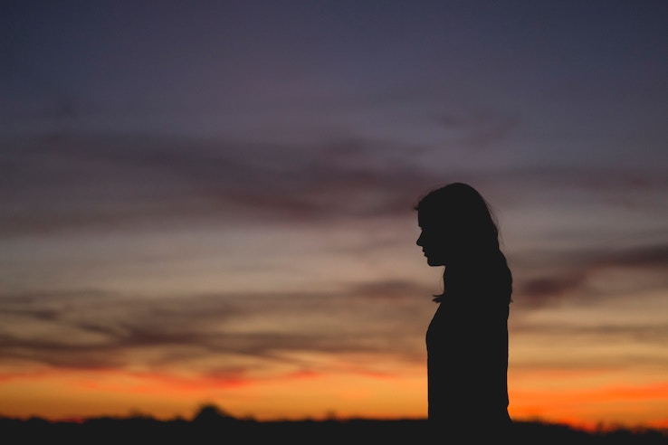A woman stands in silhouette against the sunset.