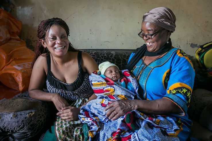 Two women smile with a newborn baby. (Photo credit: Harmony Chi)