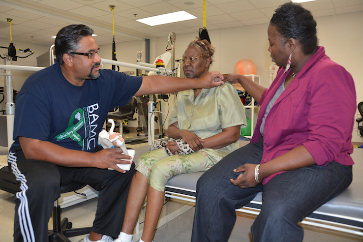 A stroke victim (center) works on recovery with a physical therapist (left) and a family caregiver (right).