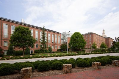 The Gillings School buildings are lined with greenery.