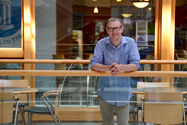 Dr. Ian Carroll poses in the Gillings School atrium.