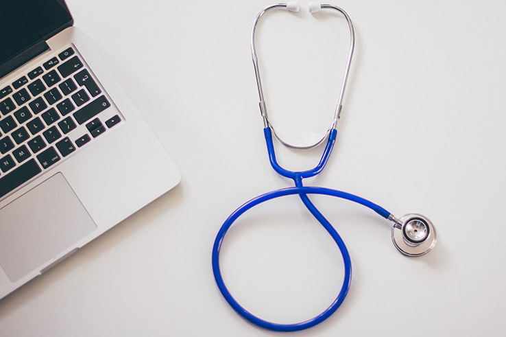 A stethoscope and computer are left on a table.
