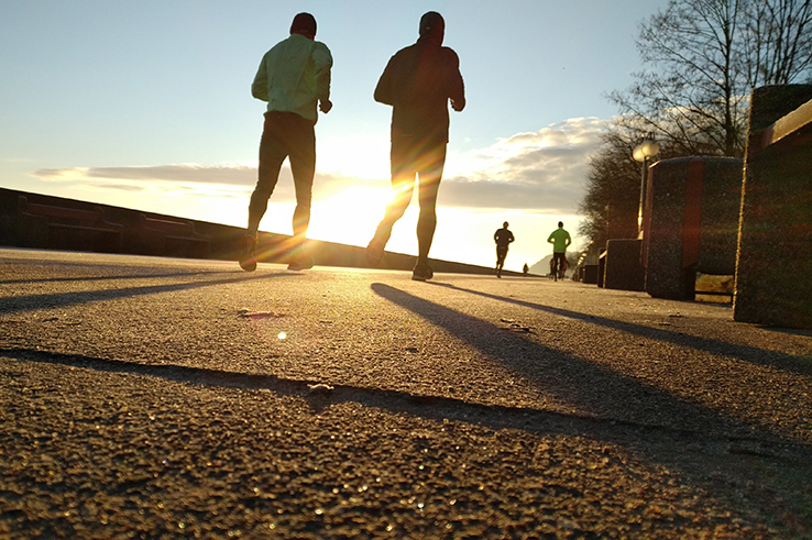 Two men jog while the sun sets.