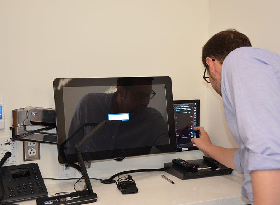 A staff member uses AV equipment.