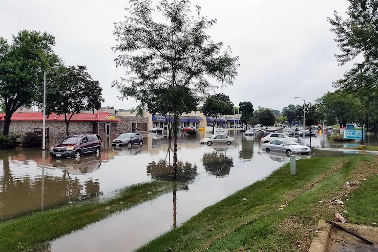Cars sit, flooded, on a public road.