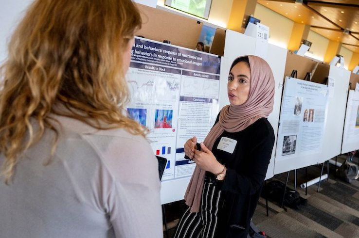 Rawan Ajeen shares her research with a curious student.