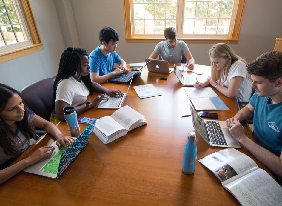 Students study in a conference room.