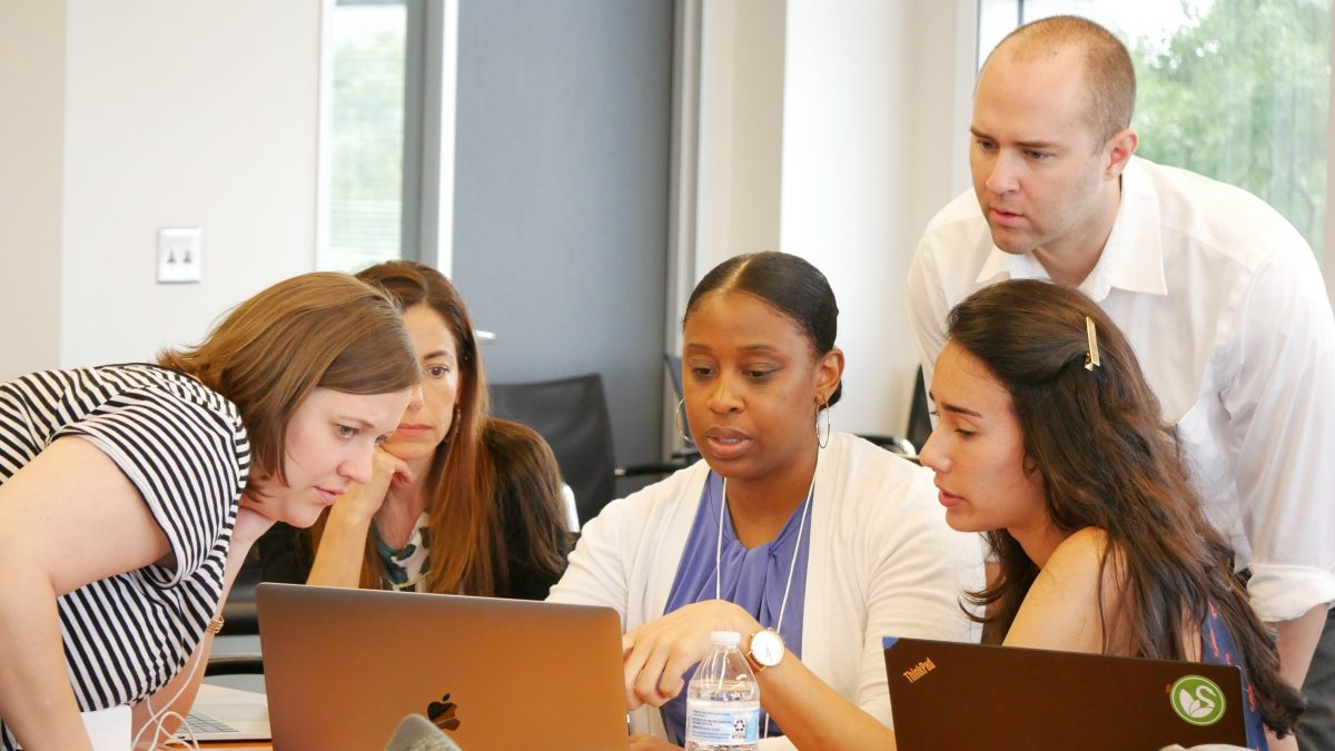 Trainees at an NCIPH workshop gather around a computer for an exercise
