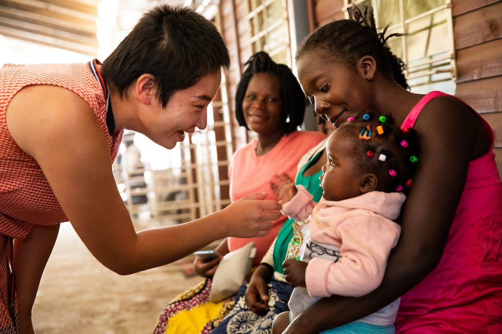 Dr. Munguu Khuyag-Ochir, a UNC Gillings student, greets a young patient in Zambia.