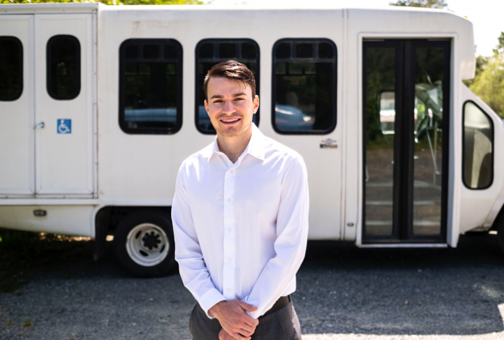 Kevin Travia stands in front of a Railcare Health shuttle bus.
