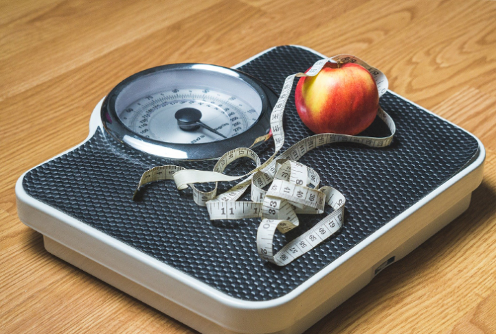 An apple and measuring tape rest on a scale.