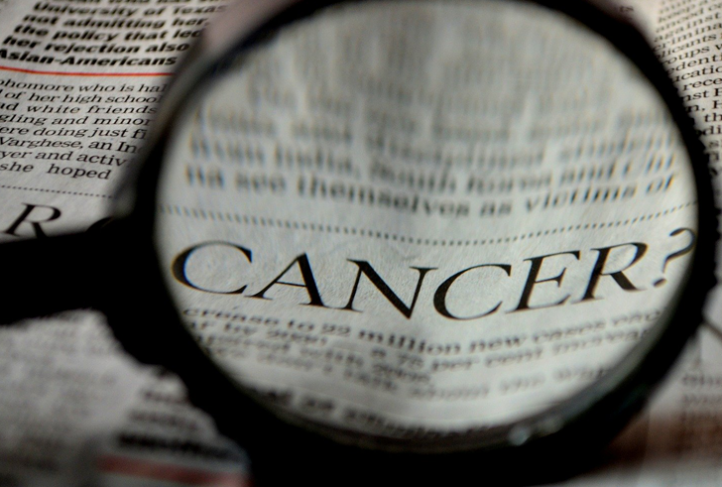Someone searches for the word cancer in a newspaper.