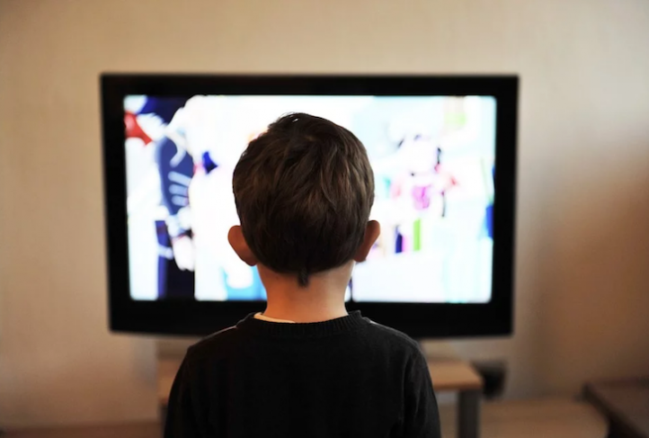 A young child stares at a television screen.