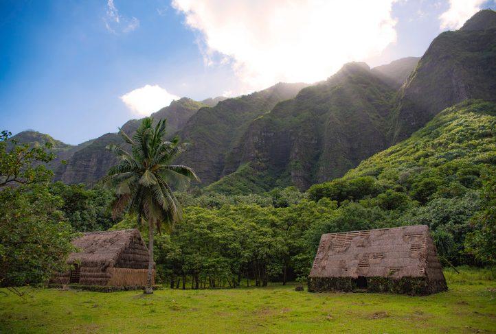 Abandoned huts dot a Polynesian landscape.